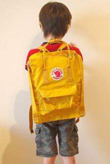 """身長120センチの子どもが背負った状態。ショルダーベルトが簡単に調整できるので、子どもから大人まで兼用で使えます。B5サイズの""""ミニ""""もラインナップしています"""
