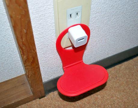 USBアダプターをコンセントに挿したら、このホルダーを付け根に引っかけて…(電気を通さない素材なのでプラグに接しても大丈夫!)