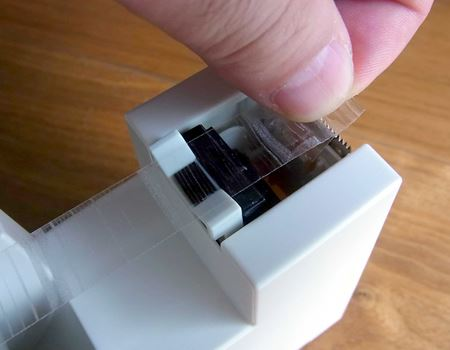 """まずは""""つまみ""""部分をつまんで引っ張ります。そして可動レバー(黒い部分)にテープを貼り付けます"""