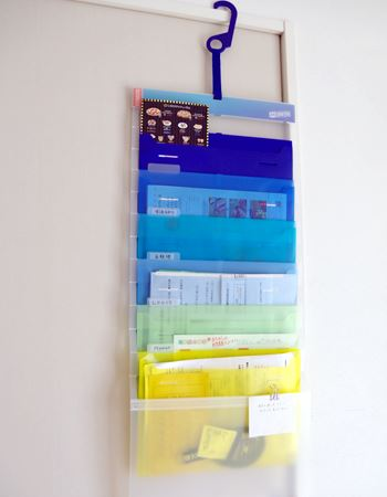 """えみぞう宅での壁掛け状態での使用例。一番下が子供からママへの""""ポスト""""。一番下の表紙の部分にはメモ用紙をクリップで留めて、忘備用や伝言用に活用しています"""
