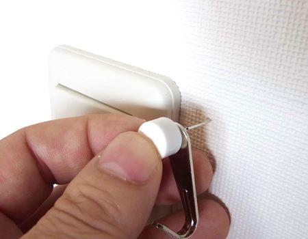 取り付け時は、フック穴にピンをとおして壁に押し込みます