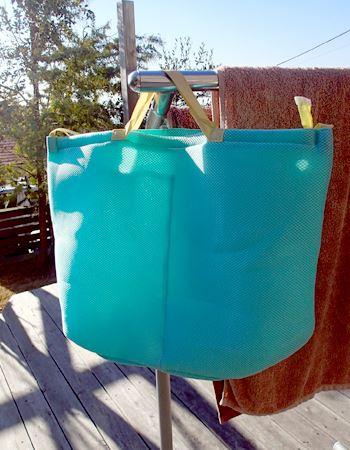干す時は両端のタグの部分を洗濯バサミで挟んで干してもOK。持ち手部分をひっかけてバッグのように吊して干してもOK。小さく畳んでも、吊しても収納できます