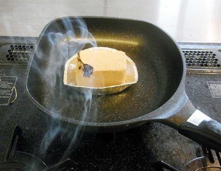 スモークウッドをライターやコンロで発煙するまで加熱したら、付属のアルミ皿の上に置き、その上から食材を並べた本体をかぶせます。今回はフライパンの上にセットしました