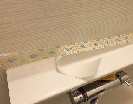 まずはバスルームの物乗せ台の上に貼ってみました。台の長辺の長さに合わせてカットした後、剥離紙を剥がします。全部剥がした後はセロハンテープの要領で両端を引っ張って伸ばしながら台の上に貼っていきます
