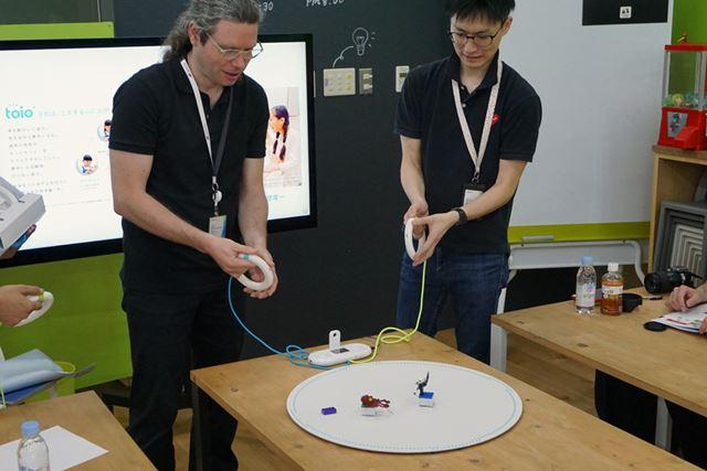 開発チームのスタッフがバトルゲームで遊んでいるシーン。互いの「toioコア キューブ」をぶつけ合って遊ぶ
