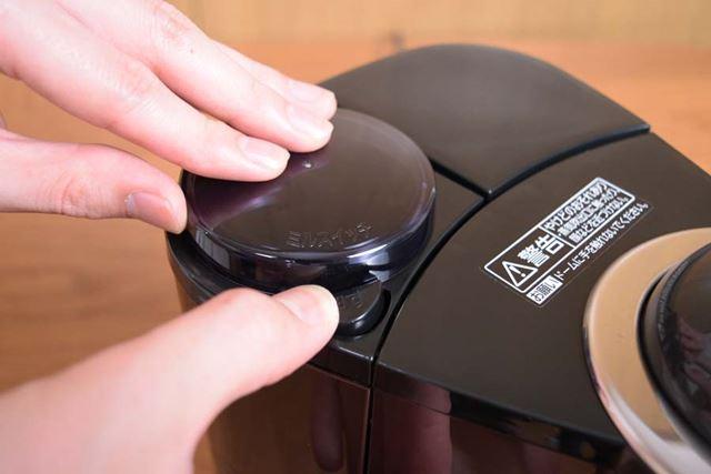 ミルふたを押さえながら手前のミルスイッチを押し、豆挽き開始