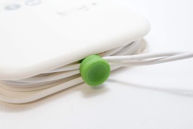 この丸い緑色の物体はゴム製で、巻き取ったケーブルを本体にまとめておくものです