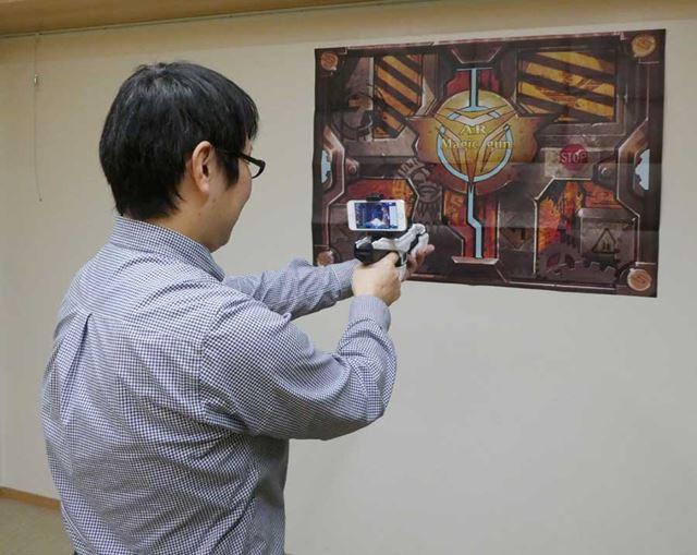 ARポスター目掛けてARマジックガンをかまえ、スマートフォン画面を見ながら敵を撃ち倒していく