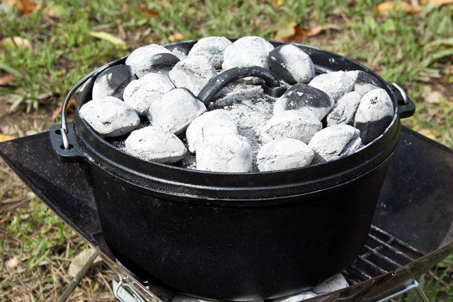 食材を包み込んで加熱するように、ダッチオーブンのフタの上に熱した炭をセット