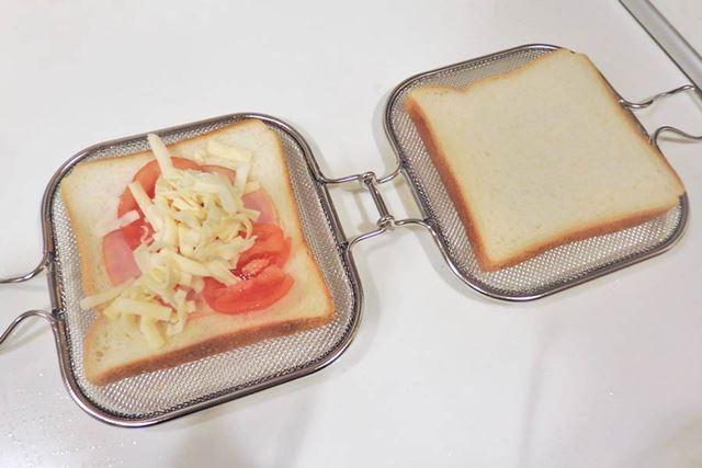 金具のロックを外して開いた面に具材を挟んだ食パンをのせて、閉じます