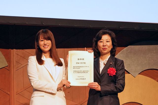 「4K8K推進キャラクター」に任命された女優の深田恭子さんに、野田聖子総務大臣から任命状が手渡された。