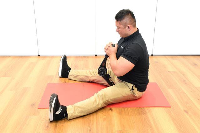 (1)マットの上に座り、片方のボールグリップを足の間の座面に固定し、もう片方を胸に固定