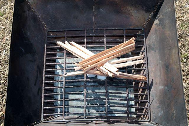 ナタで割り箸ほどの太さに割った薪を着火剤に載せます