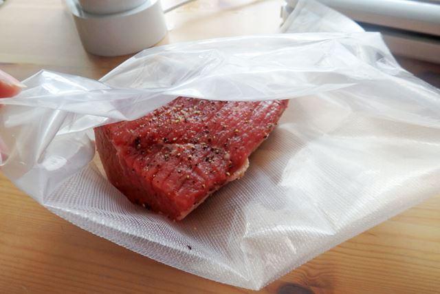 牛モモ塊肉(350g)の表面に塩こしょうをふりかけ、専用の袋に入れます