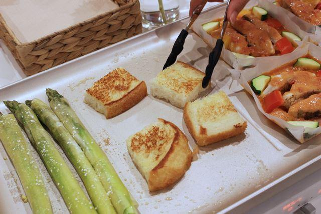 右側で保温したまま、左側のプレートで春巻きの皮で巻いたアスパラと食パンを焼きます