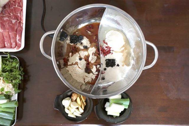 鍋に火鍋の素を入れて、切った長ねぎ、にんにく、ショウガを入れます