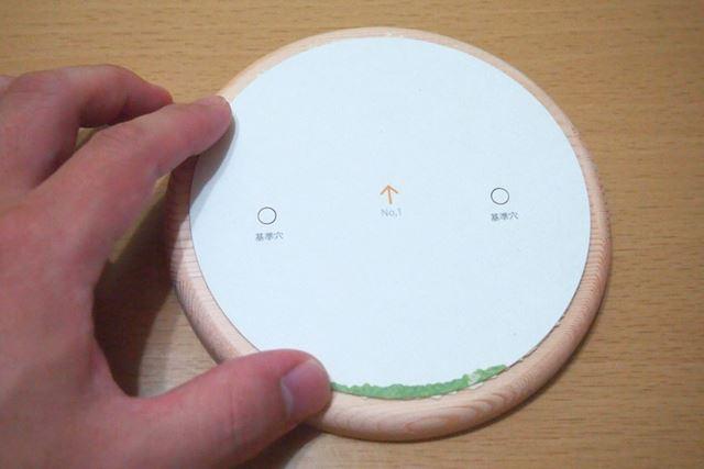 シートから保護紙ごとパーツを切り離し(上)、台座に置いて余白の広さを確認してから貼り付けます(下)