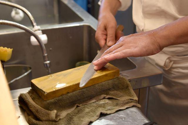 片刃の包丁の刃の部分を砥石に押し付けるようにして