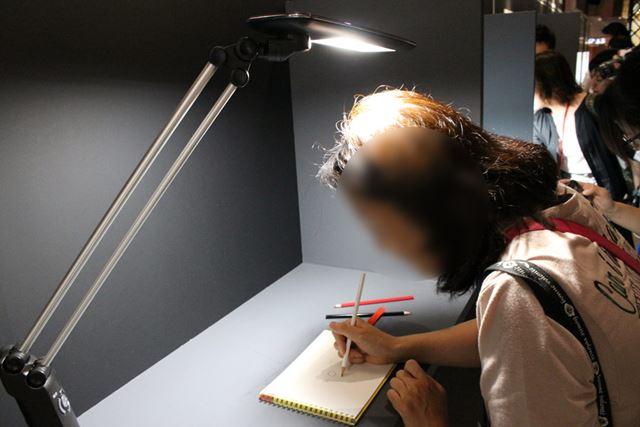 一般的なバー型のデスクライトで試してみたところ、書いている部分に濃い影が!