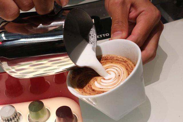 コーヒーが入ったカップに、フォームミルクをゆっくりとそそいでいきます