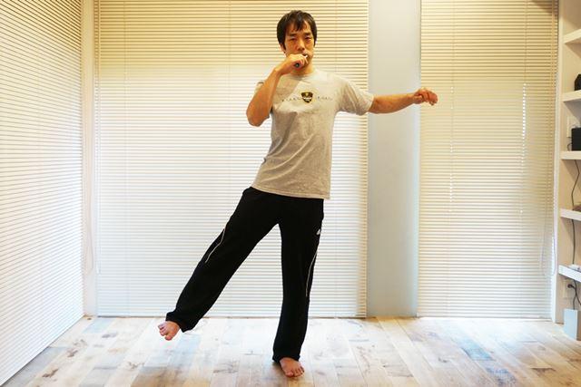 2.片足を浮かせて外側に開く。それと同時に、対角側の腕を上げる
