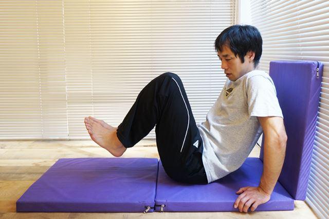 2.両手とお尻で体を支え、足を浮かして膝を胸に引き付ける