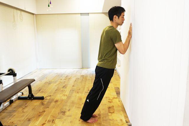2. 壁についているほうの手に体重をかけながら、腕立て伏せの要領で腕を曲げていく