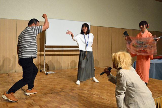 ジャンケン大会を勝ち抜き、手作りの記念品を獲得した舛田さん(写真右)