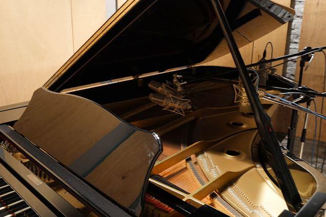 ピアノに向けられた4つのマイク。響板のフレームと弦に2本ずつ使用している