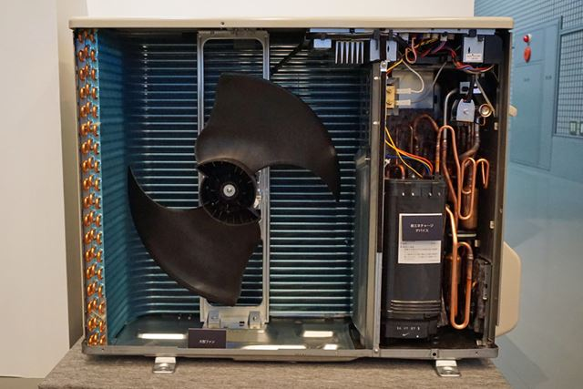 暖房運転時に室外機から排出していた熱を向かって右側の黒いデバイスに蓄え、霜取り運転に有効活用します