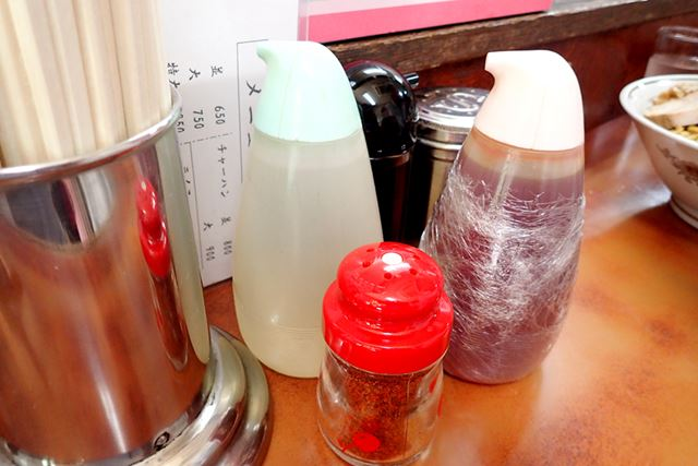 卓上には、自家製ラー油や酢といった調味料が置かれています