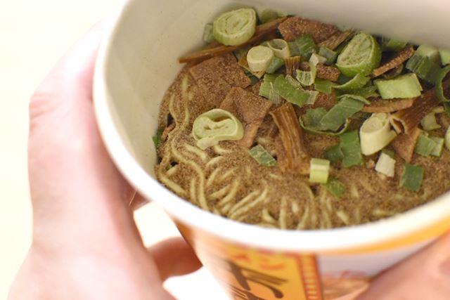 カップの中には、粉末スープに加えて、チャーシューやメンマ、大きめに切られたネギが入っています