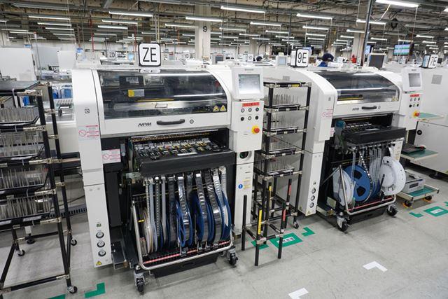 プリント板製造で部品を実装する装置。QRコード読み取りによる装着データ変更の自動化が行われている